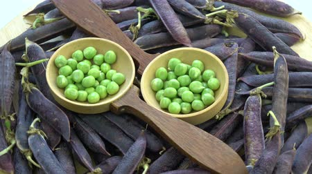 bezelye : Rotating green peas in wooden spoons and fresh violet pea pods food background