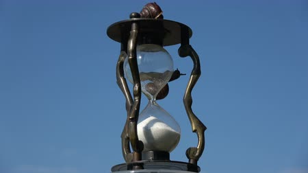 metaphors : Rotating retro hourglass sandglass with two snail and sand motion on sky background