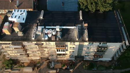 dach : Old apartment building roof  with repair equipment and scaffolding, aerial view