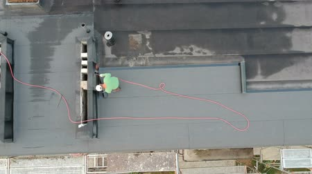 dekarz : Worker on flat roof fixing waterproofing material, aerial view Wideo