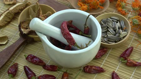 natural spicy : Rotating mortar pestle with  dried chili peppers, medical herbs, sunflowers  and mushrooms on bamboo mat Stock Footage
