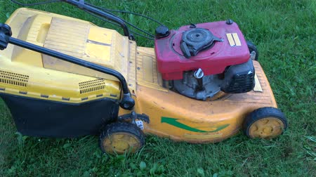 mow : Gardener manually starting old lawn mower and cut grass Stock Footage
