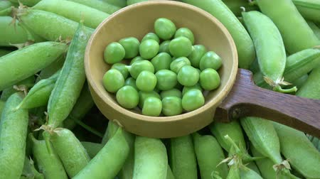 bezelye : Rotating green pea pods and peas in old wooden spoon