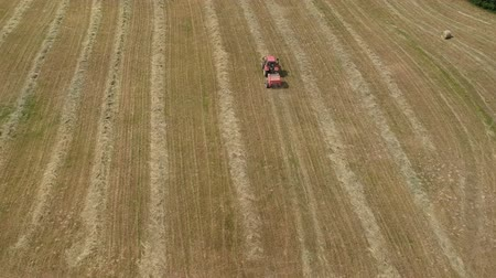 Agriculture tractor rolling dry hay bales on meadow, aerial view