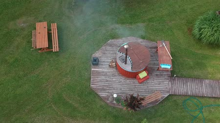 beczka : Hot water tub  near wooden bathhouse and pond, aerial view