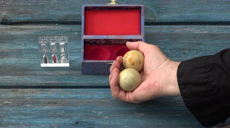yin and yang : Chinese hand massage Baoding balls in hand and hourglass on old wooden garden table