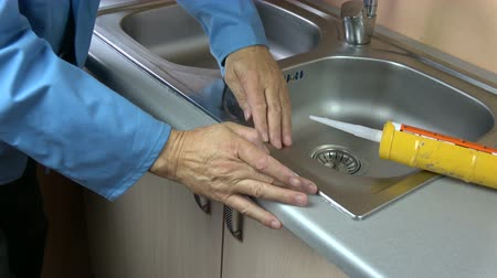 Worker hands fix sealant silicone level on washbasin  in kitchen 動画素材