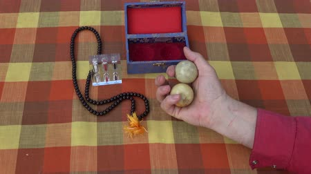 dois objetos : Chinese hand massage marble balls in hand, hourglass and Buddhist rosary