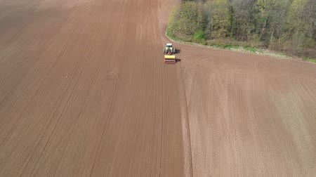 agrarian : Agriculture tractor sowing crop on farm field, aerial view Stock Footage