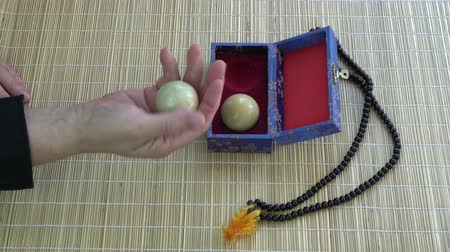 yin and yang : Opening box with Asian chinese hand massage marble balls  and Buddhist rosary on bamboo mat