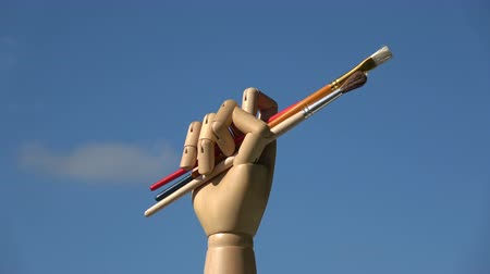 marionetka : Rotating wooden artist art manikin mannequin hand on sky background  holding paintbrushes
