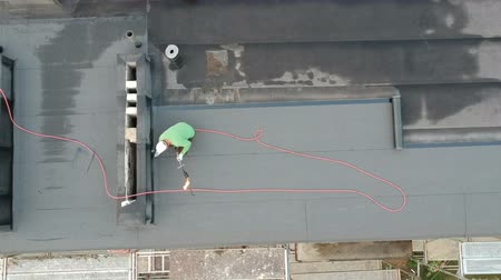 covering : Worker repair flat house roof, aerial view Stock Footage