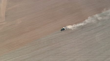 Agriculture tractor sowing crop on dusty farm field, aerial view