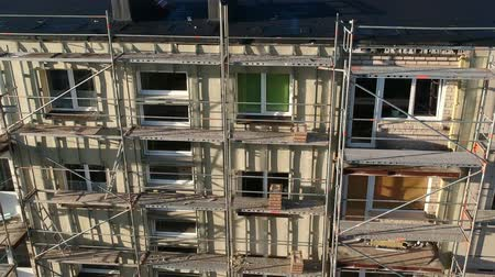dach : Drone fly up near Flat house with repair scaffolding, insulation works, aerial view Wideo
