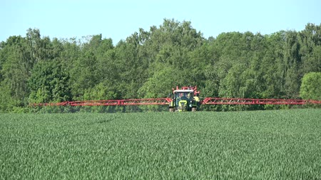 herbicides : Panevezys district, Lithuania – May 2017: Agriculture tractor spraying crop field in summer time Stock Footage
