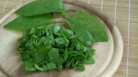 szpinak : Rotating fresh healthy chopped cutted spinach leaves on wooden chopping board
