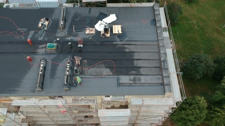 Two workers repair flat house roof in city, aerial view Stock mozgókép