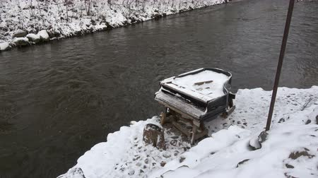 hanyatlás : Broken old snowy piano musical instrument near winter river in city Stock mozgókép