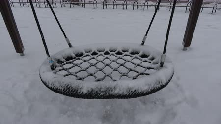 leegte : Empty snowy swing motion in city park Stockvideo