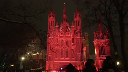 peoples : First Vilnius light festival, Church of St. Anne in red light and peoples at night, 2019 Stock Footage
