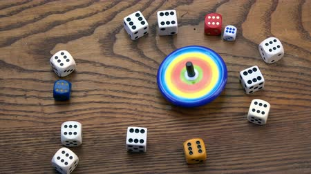 retorcido : Various game dice collection on oak background and one metal whirligig top spin in motion Stock Footage