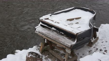 teclas de piano : Old snowy piano musical instrument near winter river in city Archivo de Video