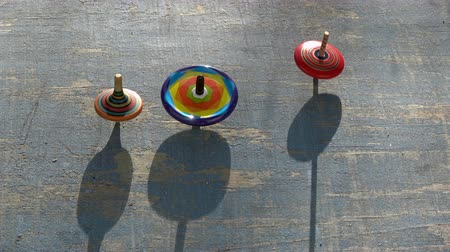 retorcido : Three colorful funny top spin whirligigs rotating on old wooden background