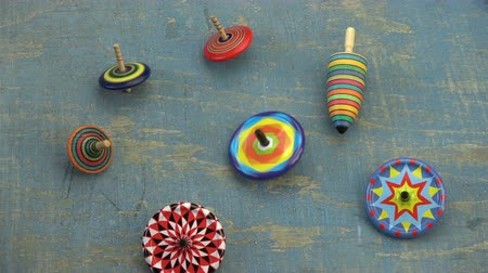 retorcido : Various beautiful colorful whirligigs top spins collection on old blue wooden table background