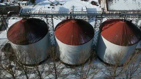 Old grain silos storage tank in province, agriculture industry, aerial view in winter 動画素材