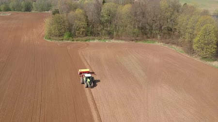 Agriculture industry. Tractor sowing crop wheat in summer end, aerial view Stock mozgókép