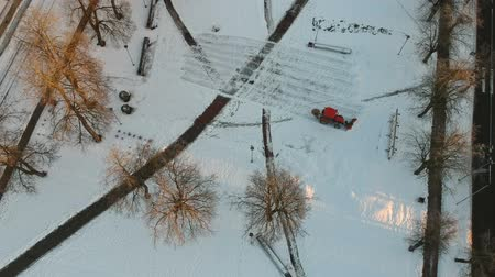 Small red tractor cleaning removing fresh snow from city park square, aerial view