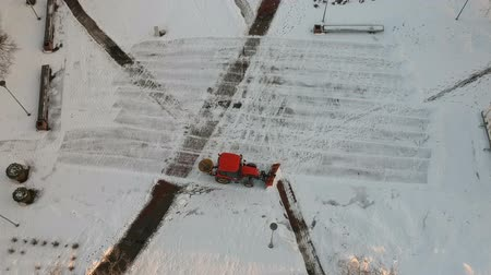 Red old tractor cleaning removing snow from city square, aerial view