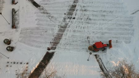 муниципальный : Tractor cleaning removing fresh snow from city square, aerial view Стоковые видеозаписи
