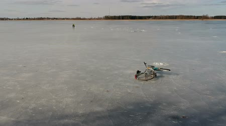 geçen : Fisherman and its bicycle on spring lake ice, aerial view Stok Video