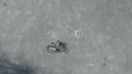 frozen lake : Fisherman  bicycle and fishing holes on spring lake ice, aerial view