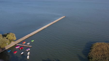golfbreker : Long concrete pier breakwater on sea lagoon, aerial view Stockvideo