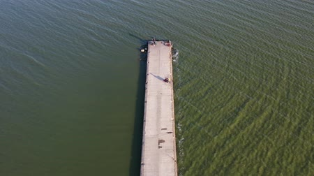 golfbreker : Long concrete pier breakwater on sea lagoon with fishermens, aerial view Stockvideo