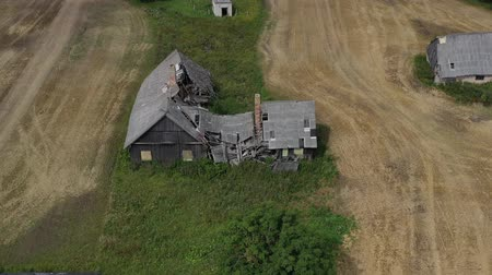desolate : derelict homestead farm house ruins on agriculture field, aerial view