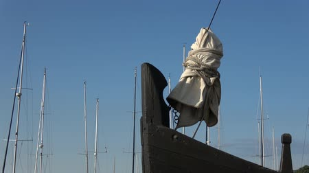 Литва : Bow of the old wooden historical ship and yachts masts in port
