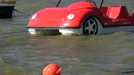 pier : Plastic red boat in shape of cars on sea water waves and orange buoy Stock Footage