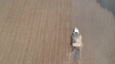 koca : tractor sowing crop on dry dusty farmland field in autumn, aerial view