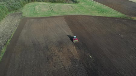 свиноматка : tractor sowing crop on  farmland field in autumn, aerial view
