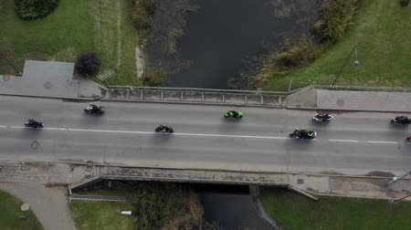 Motorcycle Bikers group on river bridge in city, closing of the season, aerial view 動画素材
