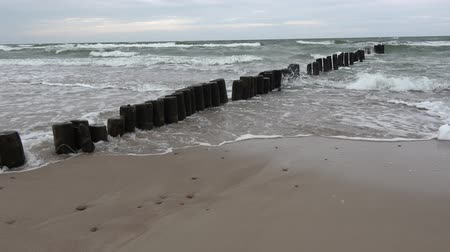baltské moře : Wooden posts jetty piles ruins  on  sea beach and waves