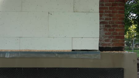 szigetelés : Historical house wall insulation with polystyrene and waterproofing foundation, zoom out