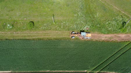leveling : Tractor grader on farmland road at work, aerial view