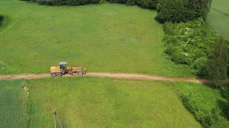 leveling : Road leveling motor grader on bad farmland road at work, aerial view