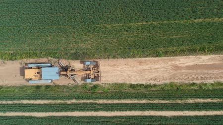 Road leveling grader on  rural gravel road at work, aerial view