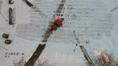 муниципальный : Red tractor cleaning removing fresh snow from city square, aerial view