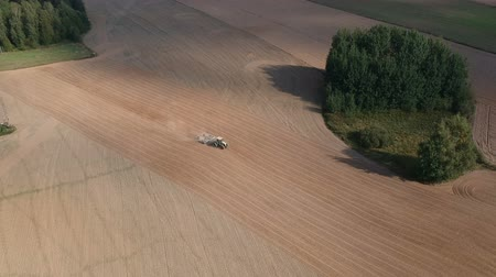 plowed land : Agriculture industry. Tractor cultivates harvested field in summer end, aerial view Stock Footage